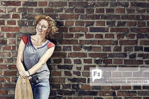 Lächelnde junge Frau mit Longboard an Ziegelmauer stehend