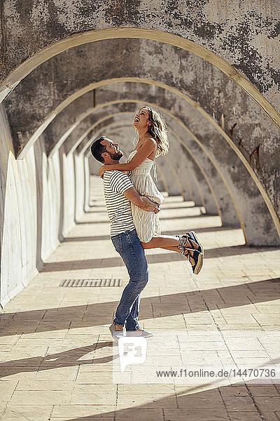 Spanien  Andalusien  Malaga  glücklicher Mann  der seine Freundin unter einem Torbogen in der Stadt hochhebt
