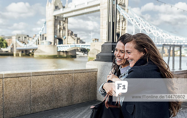 UK,  London,  two happy women near the Tower Bridge