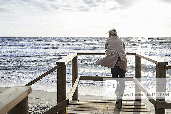 Spain  Menorca  back view of senior woman standing on boardwalk in winter looking at the sea