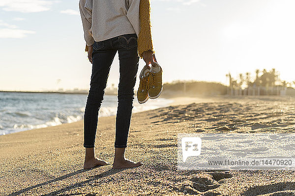 Barefoot woman on the beach  carrying her shoes