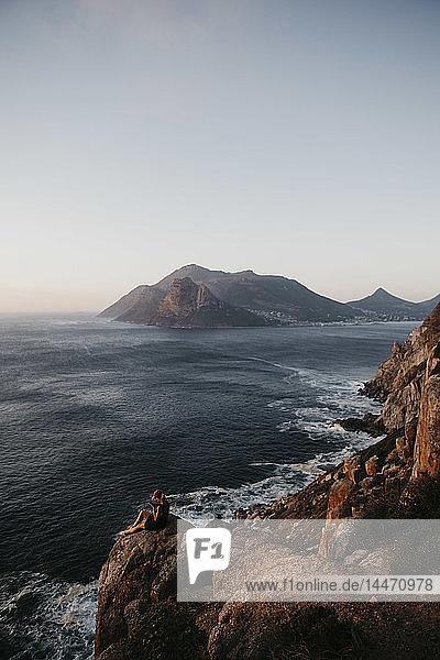 Südafrika  Westkap  Frau sitzt auf einem Felsen und benutzt ihr Handy  gesehen vom Chapman's Peak Drive