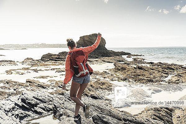 Junge Frau wandert an einem felsigen Strand