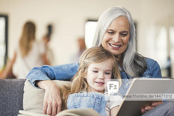 Großmutter und Enkelin sitzen auf der Couch und lesen gemeinsam
