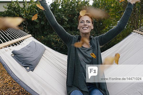 Sorglose Frau in Hängematte wirft Herbstblätter