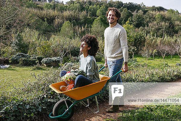 Frau sitzt in Schubkarre  hält frisches Gemüse  Mann schiebt sie