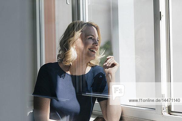 Glückliche blonde Frau im Sonnenlicht  die aus dem Fenster schaut