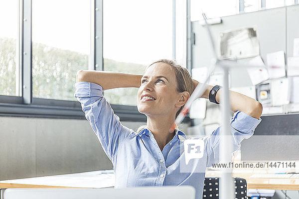 Lächelnde Frau im Büro mit dem Modell einer Windkraftanlage im Vordergrund