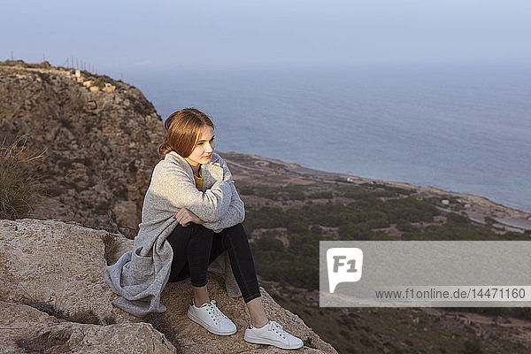 Spain  Alicante  Santa Pola  Cape Santa Pola  young woman sitting on rock at sunset