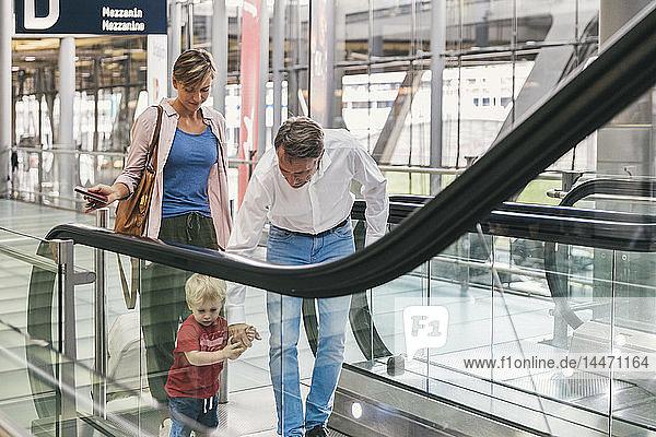 Familie auf der Rolltreppe am Flughafen
