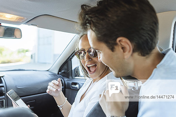 Happy couple in car with man on back seat and woman with cell phone on front passenger seat