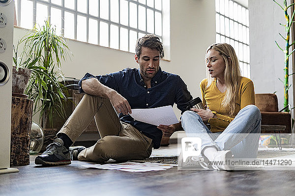Businessman and businesswoman sitting on the floor discussing documents in loft office