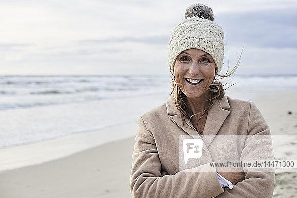 Spain  Menorca  portrait of happy senior woman on the beach in winter