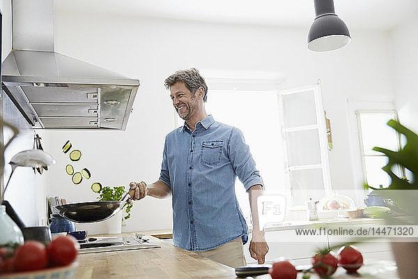 Reifer Mann brät in seiner Küche Gemüse