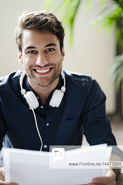 Portrait of smiling young man with headphones holding papers