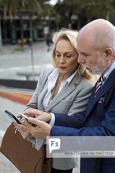 Leitender Geschäftsmann und Geschäftsfrau  die in der Stadt Mobiltelefone benutzen