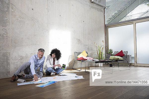 Geschäftsmann und Geschäftsfrau sitzen in einem Loft auf dem Boden und diskutieren über Dokumente