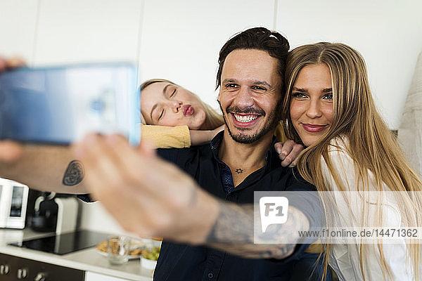 Freunde haben Spaß daran  in der Küche zu stehen und mit ihren Smartphones Fotos zu machen