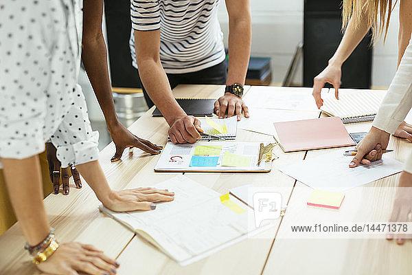 Nahaufnahme von Kollegen  die am Schreibtisch im Büro zusammen arbeiten und Papiere diskutieren