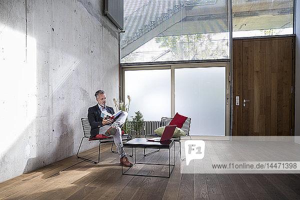 Geschäftsmann sitzt auf einem Dachboden an Betonwand und liest Buch