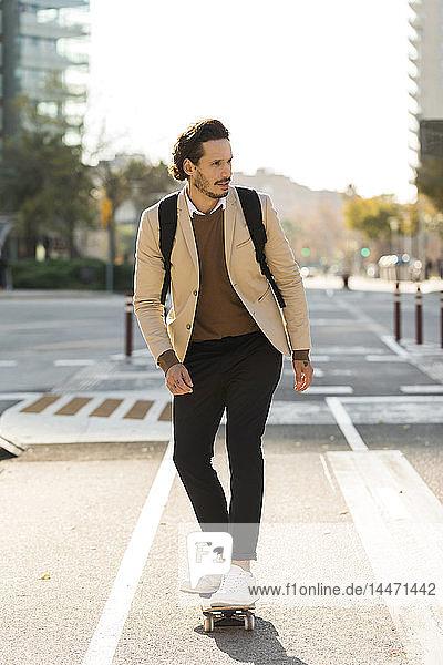 Mann mit Rucksack beim Skateboarden in der Stadt