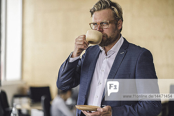 Businessman standing in office  drinking coffee from a wooden cup