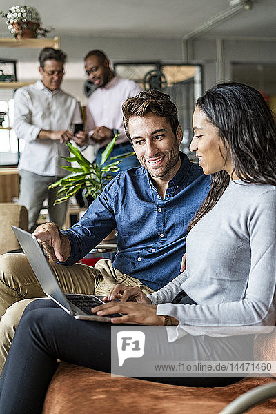 Smiling businessman and businesswoman using laptop on sofa in loft office