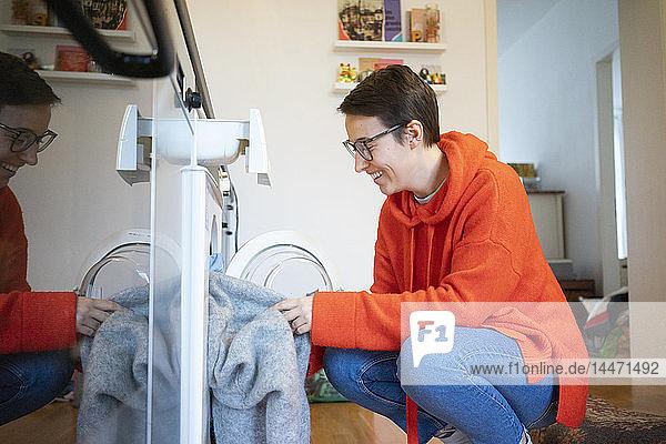 Junge Frau wäscht die Wäsche zu Hause