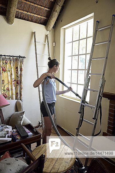 Young woman renovating her home hoovering