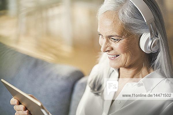 ältere Frau mit digitalem Tablett und Kopfhörern