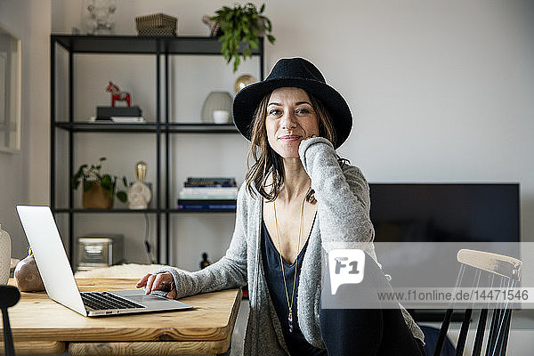 mature woman with hat  sitting at home  using laptop