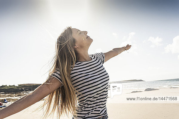 Happy young woman dancing on the beach