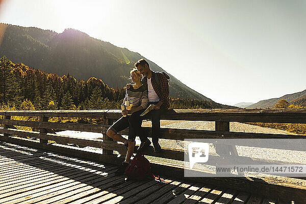 Österreich  Alpen  Ehepaar auf einer Wanderung mit Rast auf einer Brücke