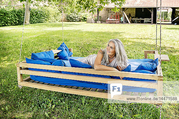 Smiling woman with long grey hair lying on a bed in garden