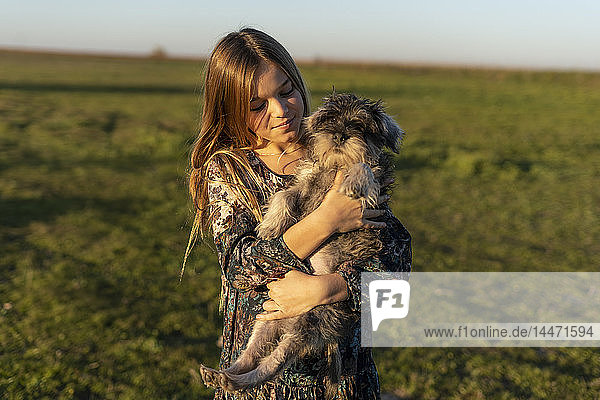 Portrait of content girl with dog on her arms at sunset