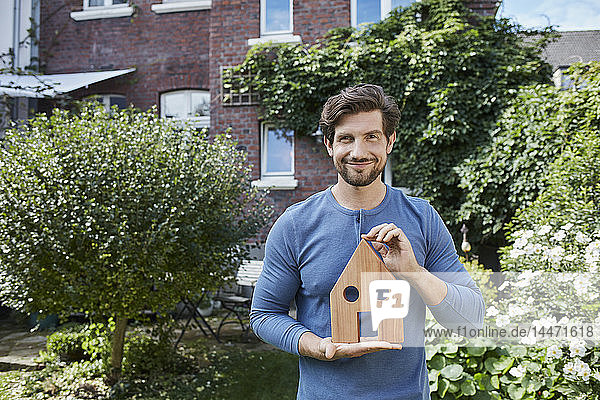 Portrait of smiling man in front of his home holding house model