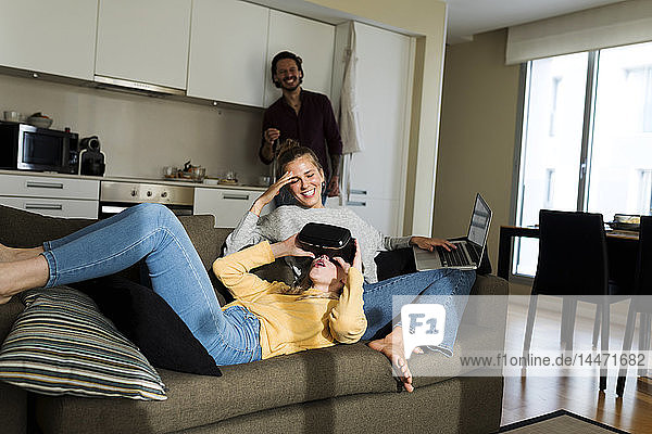 Friends sitting on couch in livingroom  gaming with VR glasses