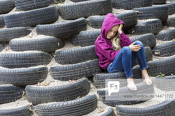 Sad girl sitting alone on playground