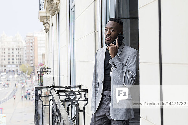 Portrait of young businessman on the phone standing on balcony