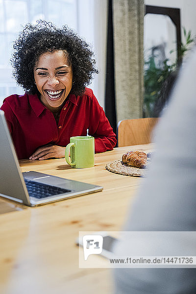 Laughing woman with laptop at table