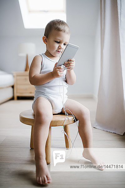 Toddler boy sitting on stool at home using smartphone
