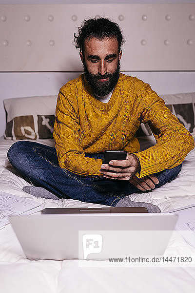Young man working in bed at home with cell phone  laptop and documents