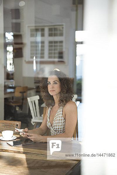 Reife Frau sitzt im Café mit Smartphone und digitalem Tablet