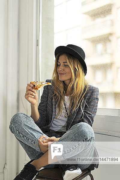 Young woman in a studio eating pizza at the window