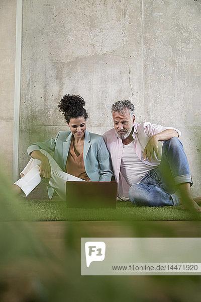 Gelegenheits-Geschäftsmann und -Geschäftsfrau sitzen auf Kunstrasen in einem Loft und teilen sich einen Laptop