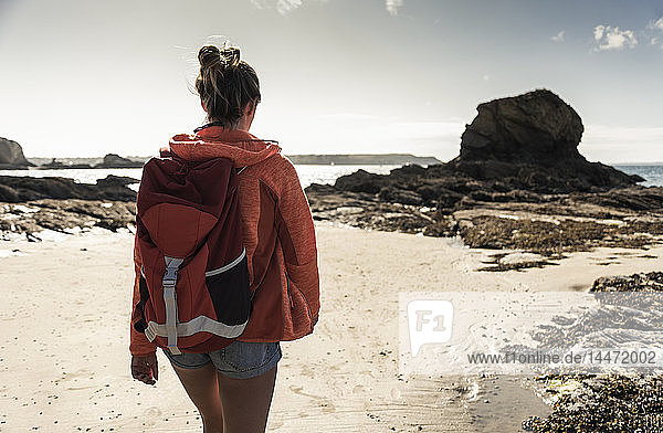 Young woman hiking on a rocky beach