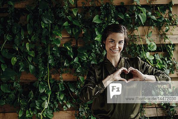Porträt einer lächelnden jungen Frau  die ihr Herz an einer Wand mit Kletterpflanzen formt