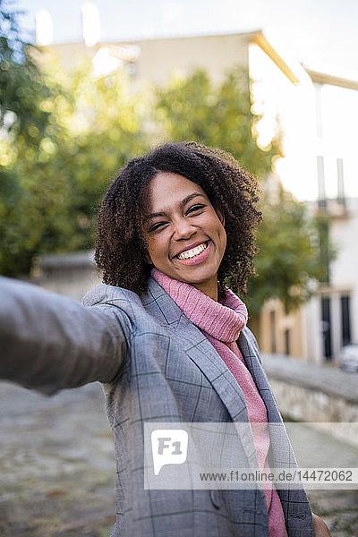Porträt einer lachenden jungen Frau  die die Hand hebt