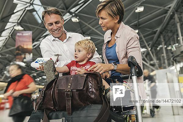 Glückliche Familie mit Gepäckwagen auf dem Flughafen