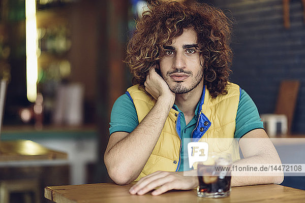 Porträt eines jungen Mannes mit Bart und lockigem Haar  der in einer Kneipe Cola trinkt